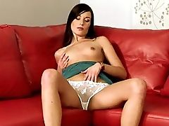 Marietta - Marietta is sitting in the corner of a cherry red leather lounge with her cream lace panties revealed, squeezing her breasts and toying with the ties to her dress. She undoes her top and starts to play with her pussy inside her panties. Removing her dress and panties, she proceeds to stick one then two fingers inside her pussy and reach for a textured vibrator with a clit tickler. She leans over the back of the couch and inserts some anal beads in her ass before returning the vibrator inside her pussy.