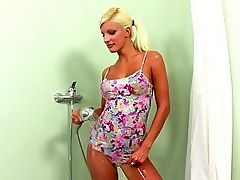 Jessy - Blonde stunner Jessy steps into the shower wearing a colorful top and matching undies, then turns on the shower and soaks her amazing body. She takes off her top and massages her firm breasts and perky nipples, then slides off her undies and uses the nozzle to spray streams of water onto her bald quim. She parts her pussy lips to show her inner pink, playfully masturbates, then crouches and pees.