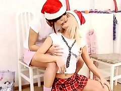 Irie and Era - Blonde Irie and her adorable pal Era are in the kitchen wearing plaid minis and Santa hats when they kiss and embrace each other passionately. They strip off their clothes and finger and lick one anothers tasty pussies, then fuck each other to intense orgasms with a red dildo.
