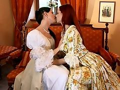 Faith and Waleria - Sultry redhead Faith and raven haired siren Waleria caress and make out passionately on an antique sofa indoors, then Faith helps Waleria off with her Victorian dress to fondle her ample breasts and erect nipples. Faith goes down on Waleria, tenderly licks and finger fucks her moist pussy to a strong orgasm. Next, Waleria strips off Faiths dress, kisses and fondles her firm tits, then slides off her undies to finger and tongue her juicy quim to a shuddering orgasm. In the end, they embrace and kiss lovingly.