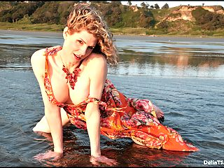 Pretty shemale cougar Delia gets wet on the beach