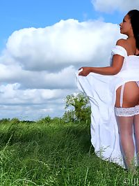 Danica Collins posing outdoors in loose cotton dress and stockings