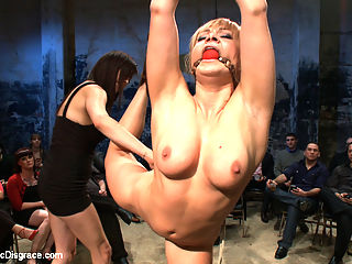 Flexible Blonde gets Bound and Fucked for the Crowd : Lea Lexus has her leg tied back in a painful arch, then has her hair tied to a hook in her ass. She is made to cum for the crowd then fucked hard in the ass and allowed to lick cum off a cake in celebration of her birthday!