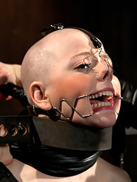 Alani Pi - Head Shaved Slut Live Show - Part 1 : Alani Pi is no ordinary model. Her cute demeanor is disarming compared to the deep and perverted girl on the interior. For her live show, she consented and even requested a head shaving. Its very unusual to get such a request. A model makes a lot of money based off of appearance, and no hair is a very extreme thing for a hot cunt like Alani to take on.Wasting no time, Alani is installed in metal stocks with her wrists trapped in leather cuffs and metal and her neck wrapped in metal. The stocks are deliberately a little high, making her chin pitch slightly upward and her legs splayed open by cuffs and straps. The idea is to make the process uncomfortable and already she is fidgeting nervously in her restraints.The electric monster clippers click on in an excited whirring frenzy. She looks calm but if you study her closely, she is trembling. Barely able to make eye contact and furtive sideways glances through her long lashes, she might be reconsidering... Claire however is very committed and starts shaving only half her head so we can see the stark comparison of shaved and not from our soon to be bald Alani. Patiently and slowly, her hair disappears and with it all ability to identify with who she previously was. Now she is just a shell... a vessel... one that we intend to fill to the brim with pain and pleasure shaping, forming, and manipulating.