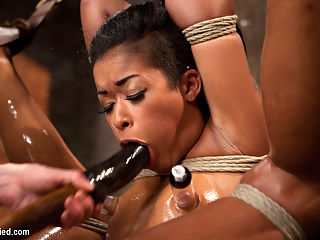 Hot and Tight Skin Diamond Pushed To The MAX At HogTied.com : Welcome amazing sultry Skin Diamond back to HogTied.SCENE 1Skin is dragged on set by Claire and bound in a suspended hogtie with her elbows together. A nice red ball gag is shoved deep into her mouth and her head pulled back tight by hair bondage. She looks furtively around as Claire torments her. The pain heightens her pleasure. Her moans rhythmic and seductive.SCENE 2Bound against a pole, Skin is suspended upside down in an extremely challenging straddle suspension. She gets rubbed with oil and glistens, showing off all of her curves and making her breasts and ass really stand out. Claire takes note and beats her so hard with the flip cat she takes most of the oil off. The cum that we squeeze from Skin is every bit as amazing as her endurance bondage.SCENE 3With her legs above her head, Skin is bound in an upright pile driver type position with her arms tied severely above her head and secured to a spreader bar. Every position has put Skin to her limit and this one pushes her the hardest. Slicked with grease and suspended in the air she is the perfect bondage puppet squirting cum slut.SCENE 4Back on the beam, her waist is bound to her thighs pushing her amazing ass out incredibly far. Her arms are bound in reverse prayer. Her hands are tied to her wrists to keep her face up and pulled back to an extreme angle. Skins head is back to far she cant even swallow! She takes it, hard. Skin Diamond is the best of the best... the best orgasms cum from the most challenging bondage - only on HogTied.com.