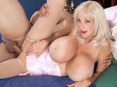 SCOREVideos Tit Attack Dee Dee Deluxx : Dee Dee Deluxxs gullible husband has left the house for the office while the devoted wife lounges around the house all day watching Oprah and waiting for delivery men to bring over their big packages. This leaves Dee Dee time to fuck neighborhood stud Tony, whos been hiding behind the bed, aching to bang Dee Dee. Tony is breastnotized by Dee Dees mega-boobs, the biggest in town, and he greedily sucks on her pointy nipples, then has her bend over from the waist to suck and tit-fuck his swollen man-horn. Dee Dees hooters dangle like gigantic bell-clappers. Dee Dees pussy was really tight, like an 18 year-olds. I was impressed, said a satisfied Tony later in the day. Dee Dee was wet from the start. She didnt need any lube. My fucking cock felt great between her boobs. Dee Dee and Minka have the biggest tits I ever busted a nut on. I dont think anyone can find women with bigger boobs than them. This was before Beshine from Germany hit iSCOREi in 2011 but Beshine is a solo model and doesnt do the nasty like Minka and Dee Dee do. Ive made an art form out of titty-fucking. I love being titty-fucked, says Dee Dee. Im into cock and ball worship. Ill fill my mouth with balls like a guy sucks on a nipple. Im not into girls although everyone wishes I was.