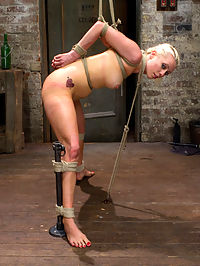 Tough Blonde Bombshell and Fan Favorite Lorelei Lee - Complete Edited Live Show : Lorelei Lee starts off her live show in one of our most brutal hogties - the pushup position! If Lorelei lowers her hands, she chokes herself with her feet tied to her neck. Closely supervised, we get to watch her live and egg her on to see how good this cum hungry whore can suck cock. She gets balls deep on Marks cock and her bright blue eyes never leave his sight. Lapping up her spit, it just keeps pouring and foaming out of her mouth. In the second position, Claire binds her in a difficult strappado hogtie and suspends her live for you in front of the camera. Mark steps in and delivers a hard blow job that Lorelei cannot escape from. Claire and Mark then fuck her face and pussy at the same time, double stuffing Lorelei, then finishing her off in a very challenging thighs only inversion that Mark face fucks her and squeezes tight hard juicy orgasms out of Loreleis ripe and willing cunt. In the third position, Lorelei is laced tightly into our brown leather arm binder and folded forward in to a straight legged pile driver with thighs to the ceiling. Add in bastinado to her tender feet and she is worked up into a frenzy. In the last position, Lorelei is bound with her wrists tied behind her back at the waist, elbows together, and knees pried wide and tied to pipe. Her nipples get the worst of it. Claire ties cruel twine to them and then to a support rope, so as her head bobs up and down on Marks cock she pulls her sensitive nipples and the twine burrows deeper into her flesh. Mark is ready to be impressed. Mark pounds his cock deep and hard into the very back of her throat making breathing impossible. She has tried desperately through the whole show to appease him, now its game time.