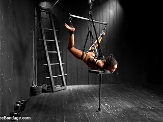Skin Diamond gets roughed up by Jack Hammer in their first scene together : Sadist Jack Hammer returns to give Skin Diamond a rough ride. They have seen each other around the armory for a long time, but the wait is finally over for Jack to deliver Skin some harsh punishment. In scene one, Skin is weaved between a series of metal poles and affixed to the pipe with clear straps. Jack puts the electrified breast cups on her tits and keeps them attached with vet wrap. To make her ability to endure more challenging, he adds the microphone attachment to her electrical predicament. If she or Jack make any noise at all, she will receive harsh shocks to her tits. Jack fully enjoys himself relentlessly tormenting Skin with her audio predicament, finding as many ways to make noise as possible. In the second position, Skin is bound in an open legged swan dive hogtie suspension with leather straps. Jack works her over with wax and adds a very mean weight to her tongue in place of a gag. In the last position, Claire thought up an evil inverted Y suspension for Skin. Her torso and thighs are strapped in a Y position and she is inverted awaiting Jacks torment... the torment of orgasm overload. Cum, squirt, more cum, more squirt, she is helpless and has no choice but to submit to his plan of orgasm overload. These positions are deceptively easy looking and very difficult to submit to. Skin did a great job enduring what seemed to be the impossible!