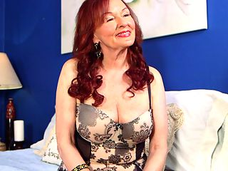 The Katherine Merlot Interview : Now its time to get to know Katherine Merlot, a 71-year-old first-timer who sat down for an interview with the 60PlusMILFs.com editor and a few invited guests. Katherine is looking super-sexy in a short dress with stockings and a garter belt, and her red hair adds to her sex appeal. Katherine was born in 1941 in Romania, the land of Dracula, Katherine says. She sounds nothing like Dracula, partly because she didnt spend a lot of time in Romania.br br Although this is Katherines first time in front of the camera, she has been an escort since she was 40 years old, a change of life that took her by surprise. We asked her how she would have reacted if, when she was 30, somebody had told her shed be here, having sex with 24-year-old men for all the world to see.br br I would have told them they are out of their minds. Its not something I ever thought about. Not then. I was married. As for the idea of being an escort, Katherine said, Im still shocked that men want to have sex with a woman my age.br br We learn a lot about Katherine in this interview. She tells us what kind of men she likes. She tells us about her pussys capacity. We find out about her very tolerant daughter. We find out about her sexual likes and dislikes.br br Gentlemen, welcome the newest star of 60PlusMILFs.com.