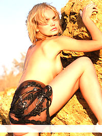 Gentle sunset : Cute blond girl poses naked on the Stony coast.