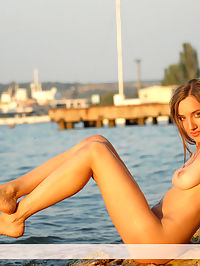 Marine tan : Nice busty hairy fox poses on the rocks of a sea bay.