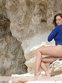 Presenting Ingret : Beautiful young girl takes off her short blue dress and shows everything near the calcareous rock.