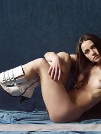 In blue : Beautiful brunet in white boots poses nude on the blue background.