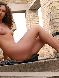 Escaliers : Young curly girl with perfect body takes her clothes off and poses on the building.