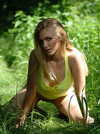 Presenting Druida : Pretty girl with a face of an angel in yellow blouse shows everything on the green fresh grass in a forest.
