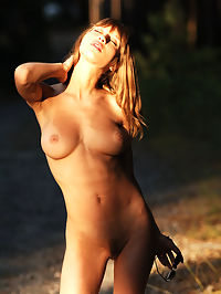 The deep : Busty girl in blue jeans shows her nice body on the forest road.