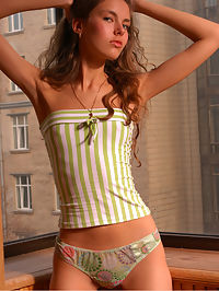 Introducing Alena : Young fresh slim beauty in striped socks poses on the balcony.