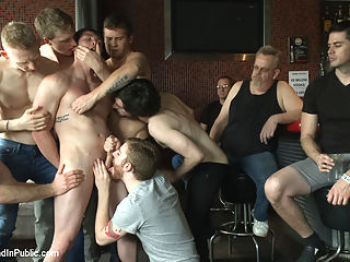 Nasty Bartender Humiliated and Gang Fucked by Angry Crowd : Everyone at the bar lines up with their cocks standing at full attention as the nasty bartender, Will Parks, is dragged in to service the crowd. As he goes from one dick to the next, the horny patrons take turns tying their shoes to his balls. Will screams for mercy as the pile of shoes pull on his stretched out balls. The crowd is unmerciful though, they line their asses up as Will is made to eat every hole with an electric butt plug shocking his prostate. Will is given the flogging of his life before everyone in the bar holds him down, each taking turns fucking his tight hole before dragging him off to the bathroom and showering him completely in cum and piss.
