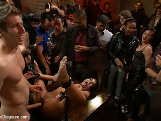 Adorable little flirt gets fucked in public! : Evi Fox is a flirtatious little lady who loves to be the center of attention. She gets dragged into a bar filled with an eager crowd who are ready to get down. Cuties from the crowd tease and torment her natural tits with clothes pins while a cock pounds her throat. She is helpless against the hitachi that never leaves her slutty clit. It is good to see her squirm.Next She gets pinned down in metal and hand cuffs to expose her whorish pussy while she is fucked hard, flogged and cattle-prodded. An audience member pounds her cunt with a dick on a stick and she simply cannot escape the torment of the hitachi.