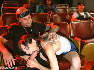 Slinky slut gives it up in an adult movie theater. : Bella Nikole Black slinks into a neon lit adult movie theater- you know the kind- where perverts go to satisfy their dark desires. She brings along her date and soon is going down on him licking and teasing his huge cock in the dim light were the other patrons can take a peek. It doesnt take long before he is parading her around for a full-on live performance of Bondage, Humiliation, manhandling, spanking, and deep-throat. She takes center stage and gets fucked hard while the audience smacks her around or just lurk around jerking off! Nikole has a hot slim body with a pair of huge tits- great to watch and eager to please.