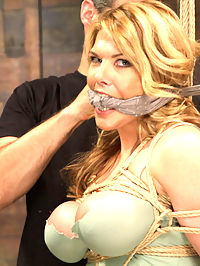 Huge Tit Blonde Bondage Slut Destroyed With Overwhelming Orgasms : Hard core bondage fans know who Carissa Montgomery is. And if not, this is the time to meet her on HogTied.Big Tit Bondage Slut is tied tight under layers and layers of rope and gags, then THREE bowling balls hung from a painful, vibrating crotch rope that gouges the FUCK out of her pretty pink snatch till she is coming over and over again, pleading for mercy.She says she loves hogties, so I give it to her good suspended, stretched open, double vibed and fucked with a giant black cock on a stick till she leaves puddles on the floor.She is so spent at this point that all she can do is lay back and get fucked. I jack her ankles in the air and open that snatch for everyone to see. When she starts to orgasms, her whole body tenses and shakes. Awesome job Carissa!