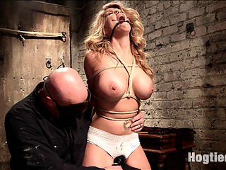 Big Tit Blonde Inescapable Orgasms : Hot slutty blonde Carissa Montgomery gets her big tits tied by Sgt. Major. Carissa is gagged and put on a brutal crotch rope before being vibed into relentless orgasms. Next Sarge has this whore tied to a post with her nipples clamped and fucked silly with a dick on a stick. Finally Carissa is put into an extreme, stressful hogtie on the floor, beat with a riding crop, fucked mercilessly and, made to cum, before being left a whimpering mess in a puddle of her own drool.