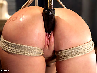 Bubble Butt Tied Tight : Jenna is so new to porn she still squeaks. We give her the full Hogtied treatment, just so she can get a feel for the pleasure and pain of rope bondage. First scene Jenna finds herself in a classic damsel in distress tie, balancing on her tippy toes with a vibrator tied against her pussy. After she endures some flogging, she is rewarded with another hitachi trapped against her clit. Second scene, it is time to take this cunt for a ride. We show Jenna a classic doggie style tie that forces her ass up, leaving her holes open to all sort of violation. Vibrators, fingers, and finally big rubber dildo all find their way into this girls pussy. The last scene is special. Jenna has never done anything with anal on camera - EVER. We cannot turn down this opportunity, and manage to squeeze a piggy tail butt plug into her virgin ass before tying her spread eagle. It is pretty entertaining watching that curly little tail bounce around her big pink ass as she screams and tries to rescue her clit from the hose. Her final lesson in bondage for the day contains something about letting go and being at peace, but really its about not being able to get your sensitive nipples and clit away from the bad man, and all those terrible unstoppable orgasms that ensue.