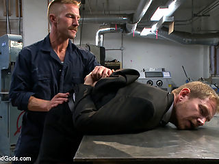 Cocky businessman bound and fucked in the metal shop : Alex Adams strolls into the metal shop as Adam Herst finishes up with his order of bondage devices. When Alex bites off more than he can chew, he finds himself bound and gagged, with his balls caught in a vice. As Alex screams from the pain, Adam shuts him up with a hard cock deep down his throat before the muscled stud is given a flogging. Trapped in his own bondage device, Alex has his hands and feet cuffed together as Adam eats the muscled studs ass. Adam then whips out his big hard cock and plows it into Alexs tight hole. After a vigorous fuck from behind, Adam flips his captive over and gives him a face full of cum.