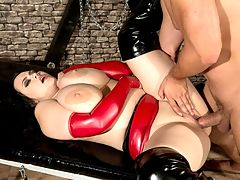 Angel In Chains : Barbara Angel is the baddest, bustiest mistress in town. Men go to her to be punished and made submissive to her will.br br All that is about to change in an epic XXX experience.br br When her slave Neeo shows up late to her fully-equipped dungeon, she digs into him for his tardiness. But Neeo is done with this charade. Its the revolt of the slave and topheavy Barbara is about to be toppled over in a dirty game that Neeo has planned.br br He seizes her riding crop, seizes her big tits and has his way with her. She resists his domination of her boobs but its too late. There is no escape. Her dungeon is now his sex workshop and Barbara is his subject. He pulls down the front of her leather bustier and gets busy manhandling those full, rich jugs.br br He orders Barbara down on her knees to fill her mouth with his boner and fuck her cleavage. Barbaras mouth oozes saliva as she deepthroats and breast-sexes his stiff prick.br br Bending her over a table, Neeo whips her ripe butt cheeks, licks Barbaras pussy and ass, finger-fucks her and, holding her tight, rams his cock into her hot cooch, spanking her ass with each thrust into her sweet spot. Her tits hang and quiver from this pounding. The Angels facial expressions run the gamut from shock to outrage to resistance to pleasure as Neeo power fucks her.br br Neeo releases Barbara from his dick domination only to sit her down on another table, lick her pussy and spank her big boobs again. He is far from finished having his way with the Angel of tits.br br A suspension bar with shackles is mounted to the ceiling. Neeo has Barbara raise her arms so he can strap her wrists to it. Then he practices his boob bondage on her delicious natural breasts with red ropes and a pinwheel sensation toy that he runs over her areolae.br br Once this little game has run its course, Barbara is brought to another table and fucked again, her pussy jammed with thrusting cock every which way. Standing, on her back, on her knees a