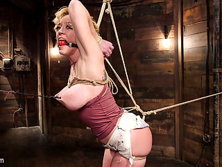 Busty Blond MILF molested in ruthless backbends : Darling is no stranger to tight rope and merciless orgasms, but this set of hard ties and ass fucking may have surprised even her. First scene finds Darlings bubble butt poking out of a pair of tiny jean shorts and her hot for teacher tits begging to be cut out of her top. Her arms are wrenched back behind her and tied to her waist, forcing her curves to draw tight against her clothing before we release them with some scissors and apply painful clamps. By the end she is securely fastened to the wall by her nipples in a painful, hobbled back arch. Second scene Darling in literally placed over a barrel, legs lifted off the ground and her already sore nipples clamped to the ceiling as her labia is sadistically spread with multiple clamps. We torment her exposed clit with vibration and fingers until she is squirting and screaming.Third scene Darling shows off her athletic body in a complete inversion, arms and shoulders weighed down with a 6x6 block of wood. As she is slowly stretched out, the tickling begins. And then the begging. And the the cumming.Final scene puts Darling in some tight ass shibari, with her hole s raised towards the ceiling with a pulley. With her face ground into a mattress and her glorious ass raised in the air there is only one thing we could do. Fuck her in the ass with every extreme toy in building until we had harvested 20 orgasms from her exhausted and helpless body.
