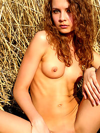 Countryside beauty : Her blonde curly hair matches wit the background as she is stretching her slender body with her boobs hard as a rock.