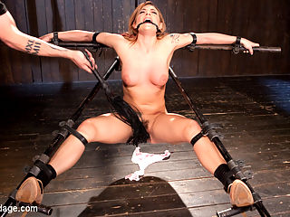Damage Me Please!! : Dahlia has gotten herself into quite the predicament this time. She is in a variation of the scavengers daughter, sitting on the ground. She is fondled and penetrated, tormented, then the device is pulled into the air. She is then put in a inverted ankle suspension with her arms and head held in place with stocks. A deprivation box is mounted to the stocks for her pretty little head to go in. She is covered in pegs, caned, flogged, and made to cum before she is let down and put into her final device.Next she is put in a brutal back bending device that shows her no mercy at all. Her body is totally exposed. The Pope starts with her feet by applying bands, then some extra special attention to her soles fills the room with screams of agony. Her body is then covered in hot wax and her nipples are tormented with a cane. Her final orgasms are monumental!!