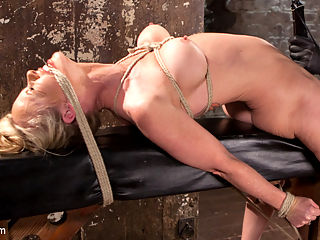 MILF Masochist in Tight Bondage : Simone is bound with her hands behind her back and her legs together. Her feet are pulled up to make her put excessive pressure on her chest, which inhibits her breathing. Her feet are tormented and her body flogged, then she is pulled into the air to endure a brutal two point suspension. Next she is on her back with her legs pulled one way and her arms the other to ensure there is no escape. She is tormented and made to cum repeatedly while in this agonizing position. In the third scene Simone is in an inverted suspension with her legs pulled wide to expose her helpless pussy. The vibe brings on a pleasurable orgasm at first, but the non stop pressure turns pleasure into suffering quickly. The final scene begins and we have Simone on her back again with her legs spread wide this time so that The Pope can destroy her pussy. She is fucked and vibed so much that it becomes unbearable, but that doesnt stop it. The orgasms flow out of this slut like water from a hose.