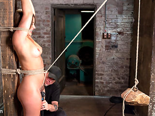 Dani Daniels in Brutal Bondage, Tormented, and Made to Cum Uncontrollably. : Danis body is pure perfection. Her tits are amazing, her ass is to die for, and her face is that of a super model. We get her tied to a post with her hands above her head to display her body. She is helpless and although she seems to be happy at the moment, this all will change quickly. A crotch rope is added with a massive rock hanging from it and suddenly the smile goes away.Next we put this slut on the floor in a very vulnerable position to be able to access her luscious cunt. Her feet get a grueling bastinado with bands until she becomes exhausted from her suffering.Dani loves to cum, so we put her in an extreme inverted suspension and tie a sybian between her legs. Its turned all the way up, her body is flogged, and we get to see this cum slut melt away into pure submissive bliss.