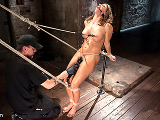 Ariel X - Extreme Bondage, Brutal Torment, and Squirting Orgasms!!! : Ariel returns after almost three years and she proves that it was well worth the wait. We begin with her in a brutal stress position that puts her toned body to the test. She is tied in a squatting position with her neck tied up to keep her from cheating her way through the scene.That is followed up with an even more intense predicament. She is made to stand on her toes with her arms back making her arch her amazing body. A crotch rope is added along with nipple clamps. The cane is introduced and Ariel finds out that there are more than the normal places that can be caned to inflict suffering.Next we put her in a side hogtie suspension that puts her on display. Her legs are tied open to ensure full pussy and ass penetration. After a several grueling minutes of torment, her pussy and ass get stuffed full of a massive dildo. Her pussy starts to show signs of enjoyment by squirting like a cock hungry slut. In the final scene Ariel is on her back and her legs spread as wide as we can stretch them. The fucking begins and this time Ariel cant help but squirt all over the room. Her squirting becomes so powerful that she begins to squirt herself in the face.