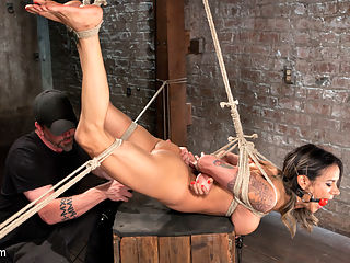Nadia Styles has an Appetite for Suffering : After quite some time away, Nadia Styles is back and ready to go. We waste no time getting her ass tied up and start the punishment. She writhes and grinds her ass into The Pope as soon as the rope touches her slutty body. Nipple clamps are added and this slut just gets more turned on, so the bondage needs to become more intense to accommodate this sluts appetite for suffering.Its clear that we are going to have to ramp the intensity of this shoot. Next Nadia is in a brutal back bending position with her ankles and wrists tied to the floor. Now we see the suffering become grueling for her. After tormenting her, she is fucked until she squirts all over the floor, then left there to suffer in the ropes.In the final scene we have her in a scorpion hogtie. Her feet are pulled high into the air, and her knees ties to keep her legs open wide. We apply nipple clamps to her and then add a little weight to increase the suffering. After some intense bastinado, we stuff her pussy with as much cock as possible for one final screaming orgasm.