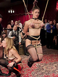 Sweet Submissive and Anal Slave Well Used : Kiki Sweet is a submissive dream sexually voracious, willing to learn, and a total rope slut. Her senior slave for the night is the minxy anal whore Mona Wales, who gleefully takes on her young charge armed with electrical torment toys and a big smile. Kiki is soon reciting the rules and to the crowds amazement picking up her feet and hanging by her hair and tits until she is told she can put her feet down. The night is filled with sounds of submissive women enjoying their play through out the room and our house slaves beg to cum while getting fucked properly in tight rope bondage. Kiki is adorable and she grovels and begs to stop cumming after her 20th orgasm. The crowd of sadistic guests only laugh at her plight and demand one more orgasm from her well used body. Mona happily steals the cock back for a rousing anal ride, covering her new slave meat in squirt and initiating another slave all in one gesture. Well done ladies!