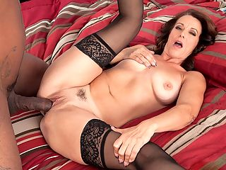 More for Mimi Moore more black cock! : When this scene opens, 43-year-old Mimi Moore, wearing stockings, panties and fuck shoes, is walking down the hall. She turns into a room. Lucas Stone is lying in bed.br br Oh, just what I wanted...a big, black cock, Mimi says in her sex doll voice, the kind of voice that will make you hard instantly. Can I suck it? I love black cock.br br She can suck it. She can fuck it.br br One of the perks of being a porn star is getting to fuck all these super-sized cocks, Mimi said after shed swallowed Lucass last drop of cum.br br Mimi is a banker from California, and, yes, she does accept very large deposits. Shes divorced. Shes a mom. She loves to fuck.br br I love to be licked. I need to have sex every day, Mimi said. The day I turned 40, it was like my sexual switch was turned on high!br br Now, despite what youre seeing here and what you might be thinking, Mimi told us, I always try to be a classic, sexy beauty. But she says the people who know her wouldnt be surprised to see her here.br br Im a very sexual creature. Im sure they could it see it coming.