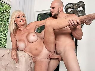 JMac shoots his load, Leah swallows : Leah LAmour is 64 years old. Shes a mother and a grandmother. Shes also a wife, and she and her lucky husband are swingers. The story of how they became swingers is pretty entertaining.br br He always wanted a threesome, like a lot of guys do, and so I tried to do a birthday surprise for him and tried to get another girl to do a threesome, but back then, society wasnt quite as open to things, and I almost ended up in jail over it, Leah said.br br Jail? br br I was calling escort sites, and I was asking them if I could hire a girl to be in a threesome with us, and they said, No, we dont do that. So, to make a long story short, I didnt get it put together, but he always wanted to do this, so five years ago, he said, Why dont we look for a threesome again? so we started looking, which brought us to the swingers sites, and thats how we ended up getting into the swinger lifestyle.br br For the record, Leah and her hubby still havent had their threesome. But Leah has fucked a lot of new men--sometimes with her husband present, sometimes with him not--and now shes fucking for the second time at 60PlusMILFs.com. Actually, the fourth time, since we film our photo sets and video separately.br br Here, this beautiful, blond GILF is walking around a beautiful house with her tits popping out of a long, sexy dress. She opens the shades and sees JMac working in the backyard. br br I love those young guys, Leah says as she calls him over. She gets up against the glass and takes out her tits, something he definitely didnt expect, and thats the signal for him to stop working and start getting to work. Before JMac knows it, hes getting his cock expertly sucked by a super-horny GILF, then hes fucking her pussy every which way and cumming in her mouth. Yeah, Leah swallows. Of course she does.br br Ive never had sex in front of the camera, Leah told us the first time she was here. Ive had sex in front of people, but I usually dont pay attention to what theyre doing. Im more focused on what Im doing!