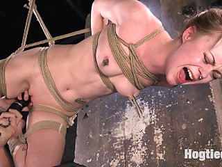 Suspension Slut Anna Tyler Succumbs to Squirting Orgasms : The stunning petite blonde Anna Tyler, dressed in little black dress and high heels is ready to surrender to her rope bondage desires. Bound and gagged, she struggles to hold back squirting orgasms as a sadistic hitachi is pushed into her tight dripping wet tiny pussy. Fully suspended, rope slicing her slit open, she screams to suffer for corporal punishment. Clothespins stinging her nipples and pinching her tongue, she is unable to resist the brutal pleasure. Finally a dick on a stick is thrust down her throat and opens up her pussy for more orgasms.