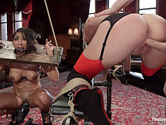 The Sex Toy and The Whipping Girl : Naughty little bitch Kacie Castle is placed on cleaning duty shining up the house property latex clad and gorgeously toned sex toy Sadie Santana. Locked in an extreme body stock, Sadie awaits sexual attention silently suffering as Kacie shines her tits and exposed cunt. As sex slaves are wont to do, Kacie over steps her bounds and is caught using the house property for her own pleasure. Severely punished with a pussy cropping that leaves her red and screaming for mercy, Kacie and made to catch the mess made from an afternoon face fucking for the sex toy. The rest of the days is a game of pain and pleasure with the sexy toy locked into hard wooden bondage and made to cum against her will, causing great punishment for Kacie involving zappers, canes, floggers, clamps and rough anal. Luckily that tough little bitch loves pain and laps up her punishment until it is her turn to teach the sex toy to ride hard cock and take it in her ass like a submissive sex object should.