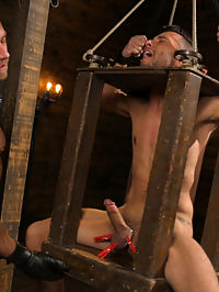 New house slave offers himself to the sexual desires of Master Colter : Dangling from the ceiling, with his head locked in a stock, Chance Summerlin awaits for house dom Jessie Colter. Master Colter inspects his boy and demands to hear how he intends to please his new master. As Chance struggles to respond, Jessie pulls on the boys cock and balls, swinging him in the air until he hears a proper response. With his gloved hands, Master Colter punches his plaything in the torso before working up his cock, only to place clothespins on his balls. Balancing on one foot, Chance struggles in his bondage with gag in mouth as his master warms him up with the flogger. Spinning back and forth, the new house slave dances in the air as the leather whip beats against his supporting leg. The gag is removed for Jessie to enjoy his boys mouth with full access, fucking the boys willing face as he swings back and forth in the bondage. Finally, Chance gets a taste of full suspension as his master fucks his ass from behind. More clothespins cover across Chances chest as the ass pounding continues, all while his master edges the boys cock in mid-air. When Jessie denies his slave of having any pleasure, he instead coats the boys eager mouth with a big load of cum. The boy begs once more for sweet release, but his master answers by leaving him dangling helplessly in the air.