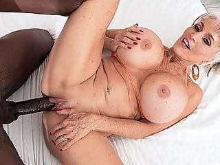 More big, black cock for super-stacked Sally : When we asked super-stacked 63-year-old Sally DAngelo to tell us one thing about her that would surprise us, she said she used to be very, very shy.br br Thats not the case anymore, at least not from what weve seen. Shes definitely not shy in this video as she rocks a micro-bikini with her curvy, huge-titted, long-legged body. Shes wearing fuck-me pumps, too, because a woman like Sally doesnt wear flats. No way.br br Then she climbs into an outdoor hot tub, takes off her top, reveals those gazongas and starts enjoying herself. Jax, the young lawn man, happens by, she asks him to join her and he does, of course. Because who could resist Sally?br br She sucks his big, black cock. Shes loud and talks dirty. He eats her pussy, and she rides his big dick, and we get great views of not only Sallys shapely ass but her asshole, too. They move inside for the fucking, Jax slams that old pussy every which way and shoots his load into her waiting mouth.br br And thats how Sally rolls!br br By the way...about shy Sally...when she was young, she fucked her boyfriend behind a couch while her father was asleep on the couch.br br She wears wild, revealing, fuck-me clothes in public.br br Ive always wanted to be in the spotlight, she said, Now I am!