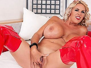 The Boobs and Boots Of A Blonde Brickhouse Brit : British super-MILF Shannon Blue said the most-fun job shes ever had was as a kennel maid I love dogs. This prepared Shannon for the boob-hounds of the world. br br Things have changed in the UK. It was the 1 place for big, natural tits. In recent times, more and more Brit women are busting out, from big to supersized. Shannon wanted huge tits. After a divorce, she went ahead and made her dream come true. She also pierced her nipples and got some tattoos.br br Ive broken a few bra hooks, Sharon said. They tend to bend under pressure. But Ive never broken a swimsuit or bikini strap. That kind of material is stretchy. Stretchy tops are what I like to wear.br br The people who know Shannon would probably be surprised to see her on iSCORELANDi. They think I am in some boring job or just doing nothing in Bulgaria. I used to be in office administration.br br Shannon is dressed in a low-cut, red PVC mini-dress over black thong panties and kinky red boots. At 59, shes a brickhouse Amazon of epic dimensions.