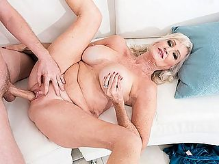 Leah LAmour does it again! : 64-year-old wife, mom and granny Leah LAmour has a problem. Shes ready to fuck. Shes good and horny. She wants dick. But her husband yep, thats her real-life hubby in this scene is fast asleep. So whats a woman to do when shes dressed for sex in her hottest lingerie? Whats a woman to do when her pussy is wet and her body is stirring? She could pull out her favorite fuck toy and satisfy herself. Heck, she could even wake up Mr. LAmour with a blow job. That would do the trick.br br But Leah has a better idea. Theres a young guy working in her garden. Leah loves em young, sweaty and hung, and she can tell by the lump in his jeans that hes packing. So she calls him inside. Tony is worried that Mr. LAmour might wake up and see them, but Leah isnt concerned. Besides, shes done this before...make a cuckold out of her hubby and suck and fuck right in front of him, that is.br br Sure enough, Mr. LAmour does wake up while Leah is sucking Tonys dick, and he doesnt seem happy about it.br br Again? Really? he says.br br Really! she says. Im in there and you dont take any time with me and Im horny and you need to learn something.br br What exactly does Mr. LAmour learn in this scene? That his wife loves to suck and fuck young cock? He already knew that. That his wife loves when guys cum on her tits? He knew that, too. That she loves to eat cum? Ditto.br br Funny thing Mr. LAmour sticks around the entire time. He doesnt leave. He doesnt try to get Tony to stop. He doesnt even threaten him. He just stands there and watches.br br So what does that tell you?