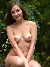Lost In The Forest : Alexandra F shows off her perky tits and hairy pussy as she poses in the forest.