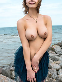 Darira : Yelena shows off her big tits as she strips by the rocky beach.